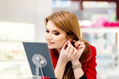Young beauty elegance woman trying earrings in the jewelry store. Thoughtful woman in the store Stock Photography