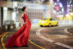 Young Beauty Famous Woman In Fluttering Red Dress Outdoor. On the big city street Royalty Free Stock Photos