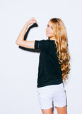 Young beauty fitness sexy blonde woman showing her muscles, her back to the camera, long hair and smiling. Indoor. Warm color. Royalty Free Stock Image
