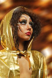 Girl in gold hood mante. Young beauty girl with art make up in gold hood of mante on light background Stock Image