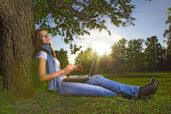 Young beauty girl with laptop in park. Photo with artistic lens flare effect Royalty Free Stock Image