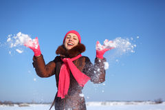 Young beauty girl outdoor in winter throws snow. Day royalty free stock photos