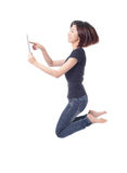 Young beauty happy jump and using tablet pc Royalty Free Stock Images