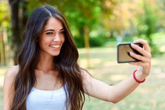 Young Beauty with long brown hair looking at smartphone Stock Photos