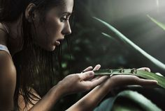 Young beauty looking at perls. Fantastic picture of delicate woman looking at perls made of water Stock Photography