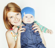Young beauty mother with cute baby, red head happy modern family isolated on white background close up, lifestyle people Royalty Free Stock Photography