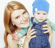 Young beauty mother with cute baby, red head happy modern family isolated on white background close up, lifestyle people Stock Photos
