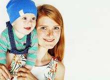 Young beauty mother with cute baby, red head happy modern family. Smiling isolated on white background close up, lifestyle people concept Stock Photo