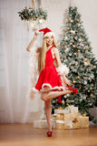 Young beauty santa woman near the Christmas tree. Fashionable lu Stock Photos