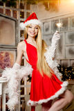 Young beauty santa woman near the Christmas tree. Fashionable lu Royalty Free Stock Photography