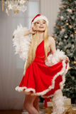 Young beauty santa woman near the Christmas tree. Fashionable lu Royalty Free Stock Photos