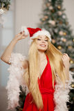 Young beauty santa woman near the Christmas tree. Fashionable lu Royalty Free Stock Image