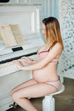 Young beauty and sexy Caucasian pregnant woman in a bright pink cream lingerie about piano on Studio. The concept of Stock Image