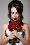 Young Beauty Smelling Bouquet of Red Roses. Pleasure & Harmony Royalty Free Stock Images