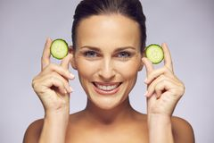 Young beauty smiling with cucumber slices. Portrait of young beautiful woman holding cucumber slices in hands near her face smiling at camera on gray background Stock Photo