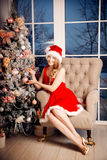 Young beauty smiling santa woman near the Christmas tree. Fashio Royalty Free Stock Images