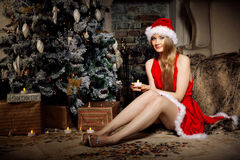Young beauty smiling santa woman near the Christmas tree. Fashio Royalty Free Stock Photos