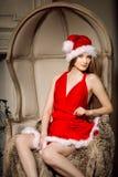 Young beauty smiling santa woman near the Christmas tree. Fashio Royalty Free Stock Photos