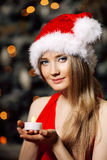 Young beauty smiling santa woman near the Christmas tree. Fashio Stock Photo