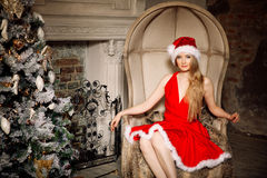 Young beauty smiling santa woman near the Christmas tree. Fashio Stock Photography