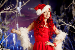 Young beauty smiling santa woman near Christmas tree. Fashionabl Royalty Free Stock Photos