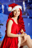 Young beauty smiling santa woman near Christmas tree. Fashionabl Royalty Free Stock Image