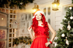 Young beauty smiling santa woman near Christmas tree. Fashionabl Stock Photos
