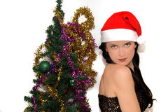Young beauty smiling santa woman near the Christmas tree Stock Photo