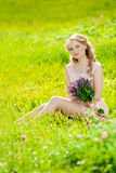 Young beauty smiling woman in the field, on the grass. Girl rest Royalty Free Stock Image