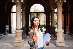Young beauty student girl with notebooks outdoors the university drink a cup of coffee. Smart intelligent grad student glasses confident happy at university hall Stock Photos