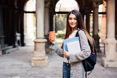Young beauty student girl with notebooks outdoors the university drink a cup of coffee Royalty Free Stock Photography