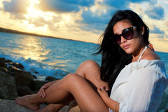 Young beauty with sunglasses sitting on a rock by the ocean Royalty Free Stock Photography