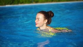 Young beauty swim in the swimming pool and smiling. Beautiful woman stock video
