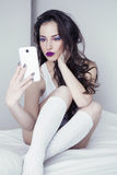 Young beauty taking selfie. Young woman with pretty makeup sitting on bed and taking selfie with her mobile phone Stock Photos