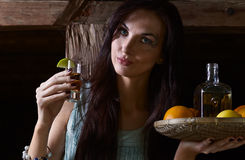 Young beauty with tequila in the old wooden house Stock Photography