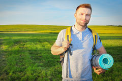 A young beauty traveler walks along a green meadow with backpack and rug. Tourist in outdoors on bright sunny day in summer Royalty Free Stock Photos