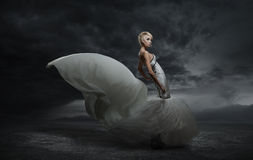 Young beauty woman. Wearing gorgeous dress standing over dark sky background Stock Photography