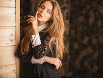 Young beauty woman against house interior. Stock Photos