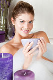 Young beauty woman in the bath drinking herbal tea. In the forefront with lilac candles Stock Images