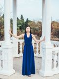 Young beauty woman in a blue dress. Walking in a park Royalty Free Stock Photo