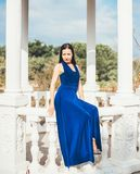 Young beauty woman in a blue dress. Walking in a park Royalty Free Stock Image