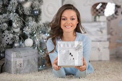 Young beauty woman with Christmas gift box, new year tree backgr. Ound Stock Images
