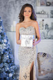 Young beauty woman with Christmas gift box, new year tree backgr Royalty Free Stock Photos