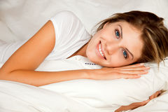 Young beauty woman couch in the bed. And smiling Stock Photos