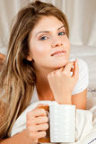 Young beauty woman couch in the bed with a mug Stock Image