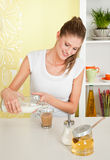 Young beauty woman dipping milk into a cup of coff Stock Images