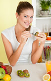 Young beauty woman eating kiwi Stock Images