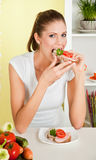 Young beauty woman eating sandwich with ham and ve Stock Photography
