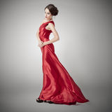 Young beauty woman in fluttering red dress. Stock Photography