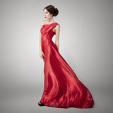 Young beauty woman in fluttering red dress. Royalty Free Stock Image